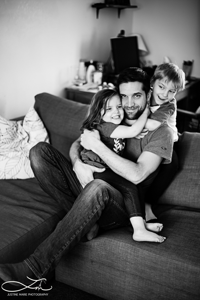 father playing with his kids on the couch in living room lifestyle
